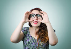 Funny girl in glasses looking hands, grimace portr Royalty Free Stock Images