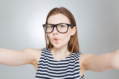 Funny girl in glasses making funny face and taking selfie. Funny cute teenage girl in glasses making funny face and taking selfie royalty free stock photos