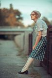 Funny girl with glasses and a vintage dress. Outdoors royalty free stock photography