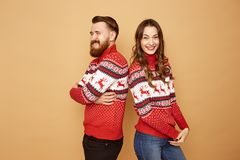 Funny girl and a guy dressed in red and white sweaters with deer stand back to back on a beige background in the studio royalty free stock photo