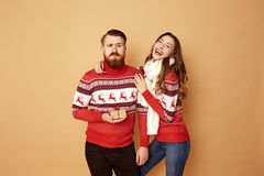 Funny girl and a guy dressed in red and white sweaters with deer stand together on a beige background in the studio stock photos