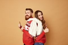 Funny girl and a guy dressed in red and white sweaters with deer and white knitted scarf stand back to back on a beige stock photos