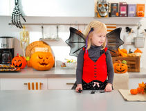 Funny girl in halloween bat costume in decorated kitchen Stock Image