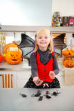 Funny girl in halloween bat costumein with mouse toys. Funny blond girl in halloween bat costumein holding mouse toy in hand in decorated kitchen. Ready to Royalty Free Stock Images