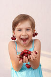 Funny girl with handful of cherries. Little girl with handful of cherries stock photo