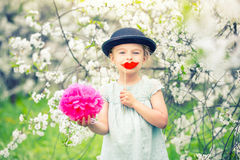 Funny girl in hat and with fake lips in spring garden. Royalty Free Stock Images