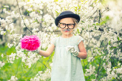 Funny girl in hat and gloves and with fake mustache. Funny girl in hat, glasses and gloves and with fake mustache playing in spring garden Stock Photography