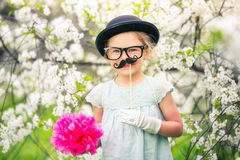 Funny girl in hat and gloves and with fake mustache. Funny girl in hat, glasses and gloves and with fake mustache playing in spring garden Stock Photo