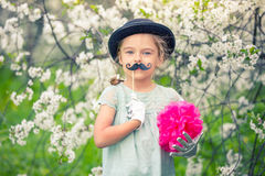 Funny girl in hat and gloves and with fake mustache. Royalty Free Stock Photo