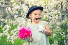 Funny girl in hat and gloves and with fake mustache. Stock Photo