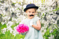 Funny girl in hat and gloves and with fake mustache in spring garden. Stock Photography