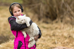Funny  girl in headphones with a cat in his hands. Stock Images