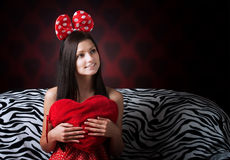 Funny girl with a heart cushion stock photo