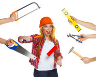 Funny girl in a helmet with different tools is isolated on the w Royalty Free Stock Image