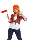 Funny girl in a helmet with roller in hand it is isolated on the Royalty Free Stock Image