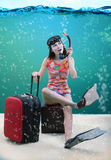 Funny girl with her travel luggage sitting under the sea. Funny portrait of a girl with her travel luggage and snorkeling equipment sitting under the sea Royalty Free Stock Photography