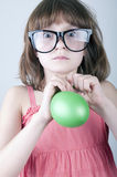 Funny girl with herd sunglasses blowing a balloon royalty free stock images