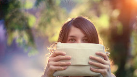 Funny girl hidding by holding a beige purse Stock Images