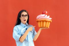 Funny Girl Holding Big Huge Giant Sweet Muffin Cupcake. Woman with a sweet tooth considering to eat huge patty cake Stock Photos