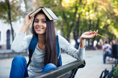 Funny girl holding book on head outdoors Stock Photography