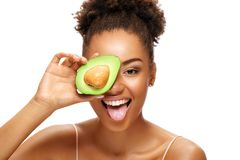 Funny girl holding half an avocado in front of her face and showing tongue. stock photos