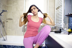 Funny girl holding long hair in pigtails in bathroom in pajamas Royalty Free Stock Photo
