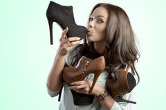 Funny girl holding many shoes Royalty Free Stock Photo