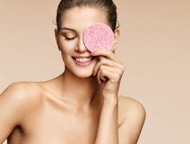 Funny girl holding pink sponge near her face. Portrait of young girl on beige background. Youth and skin care concept Royalty Free Stock Images