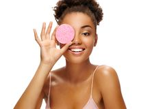 Funny girl holding pink sponge near her face. Portrait of young african american girl on white background. Youth and skin care concept stock photo