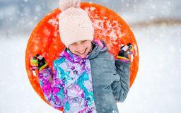 Funny girl with saucer sled outdoors Stock Photography