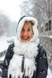 Funny girl in the hood and white scarf shows her tongue. In the snow weather. winter entertainment royalty free stock image