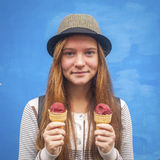 Funny girl with ice cream in hand on the blue wall background. Stock Photography