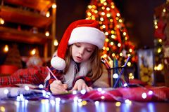 Funny Girl In Santa Hat Writes Letter To Santa Royalty Free Stock Photos