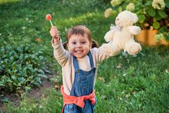 Funny little girl jumping for joy.a young child in denim overalls. Funny girl jumping for joy.Fun little girl running in denim overalls. Cute beautiful child Royalty Free Stock Photography