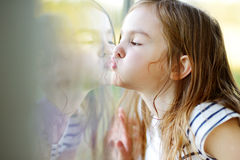 Funny girl kissing her reflection on a window Royalty Free Stock Photography