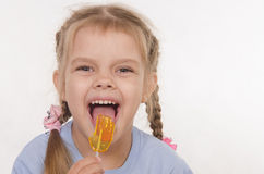 Funny girl licking a lollipop Stock Photography