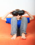 Funny girl. Little girl - funny barefoot kid in jeans and blue t-shirt sitting on orange couch and playing with black plastic pots as with glasses or telescope Royalty Free Stock Photos
