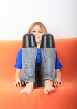 Funny girl. Little girl - funny barefoot kid in jeans and blue t-shirt sitting on orange couch and playing with black plastic pots on knees Stock Images