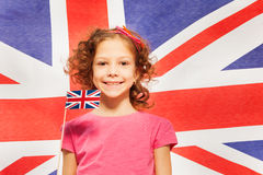 Funny girl with little flag against British banner Royalty Free Stock Images
