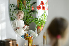 Funny girl looking at herself in a mirror Stock Image