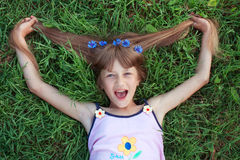 Funny girl lying on the grass and pulling her hair with cornflow Royalty Free Stock Photo
