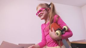 Funny girl with magic wand and skateboard. In room stock video footage