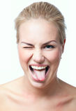 Funny girl making faces. Funny cute blond woman making faces, showing her tongue, winking, looking at camera. Isolated on white Royalty Free Stock Photography