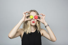 Funny girl making faces with two macaroons placed instead of eyes. Girl has curly blond hair and looks sexy. Stock Photos