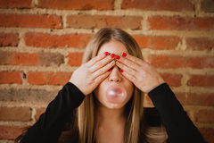 Funny girl making a pomp with a bubble gum Stock Photos