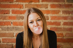 Funny girl making a pomp with a bubble gum Royalty Free Stock Photography