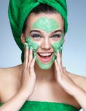 Funny girl with moisturizing cream on her face Stock Images
