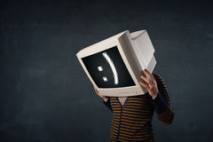 Funny girl with a monitor box on her head and a smiley face Stock Photos