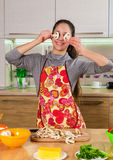 Funny girl with mushrooms slices on eyes making the pizza Stock Images