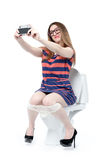 Funny girl photographs herself sitting on the toilet. Stock Photos